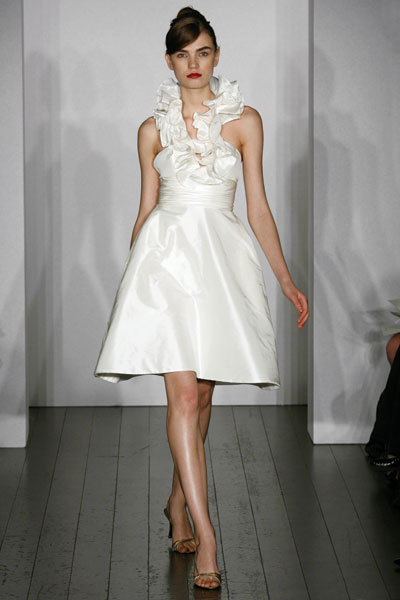model on a catwalk with a short white wedding dress