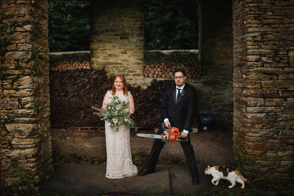 destination wedding in a barn Aislinn Events groom with chainsaw and bride with bouquet