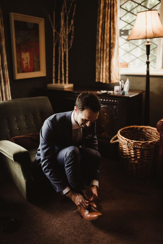 Family Fun in Glengarriff elopetoireland.com groom putting on his shoes in his room with a wicker basket