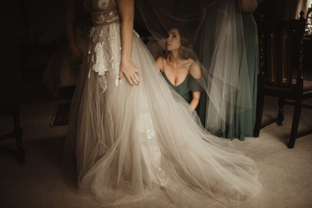 Family Fun in Glengarriff elopetoireland.com bride having her dress fixed by bridesmaid