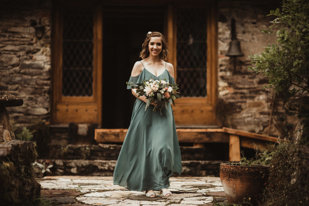 Family Fun in Glengarriff elopetoireland.com bridesmaid with blue bridemaid dress and bouquet of flowers