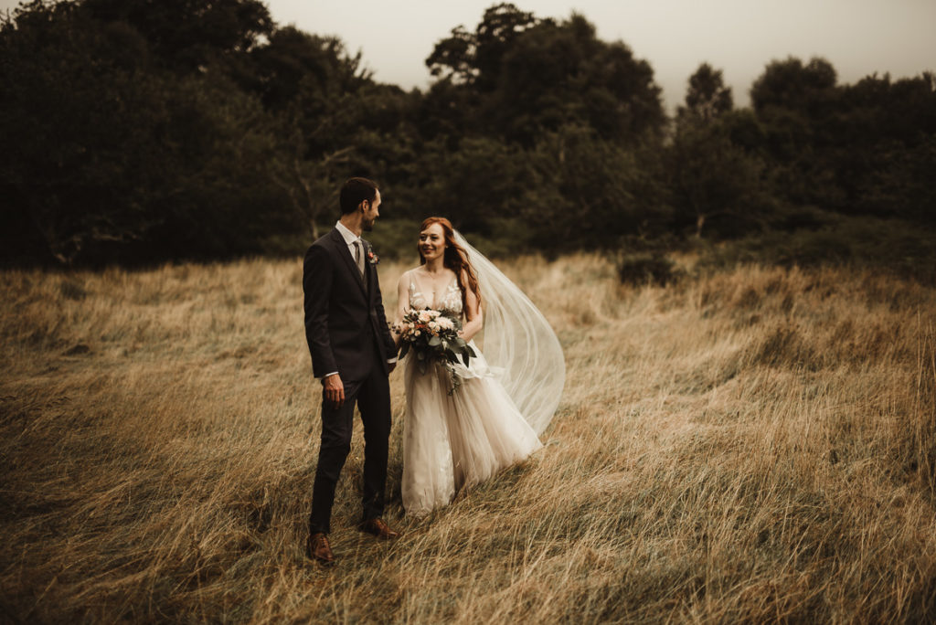 Family Fun in Glengarriff elopetoireland.com bride and groom in a field of grass